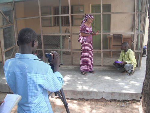 On set of the Duniya Juyi Juyi movie. Almajirai playing the roles of cameraman and actor. Photo credit: Carmen McCain's Flickr photos